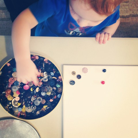 Be still my heart. Our little man making his first button art project.