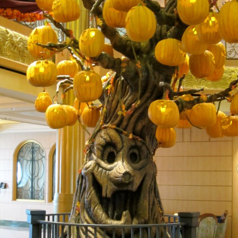 This is the Halloween Tree on the Disney Fantasy cruise. It develops through the course of the cruise. When you board, it's just the smiling tree. Later, jack-o-lanterns appear and towards the end of the cruise, the jack-o-lanterns light up. There's Halloween story-time around the tree on various nights.